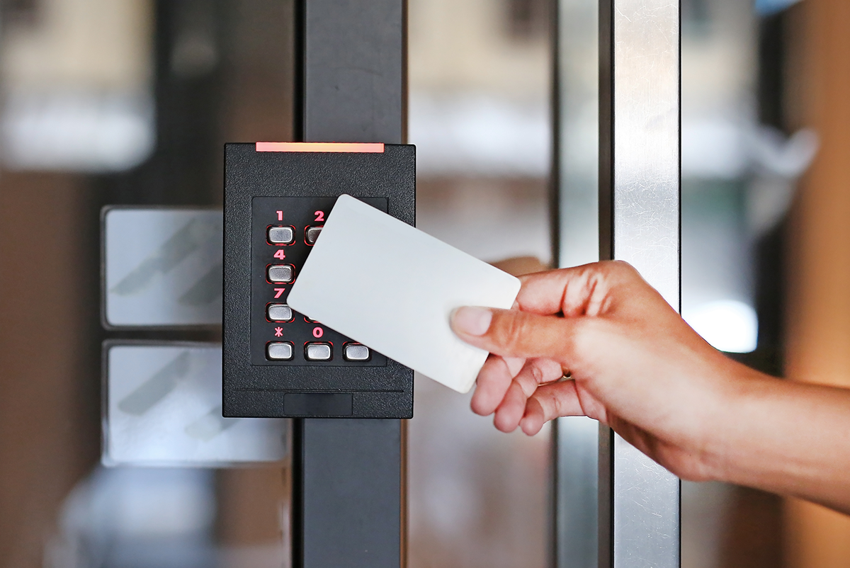 A door access control system. An office worker is scanning an entry card reader to access a secured building.