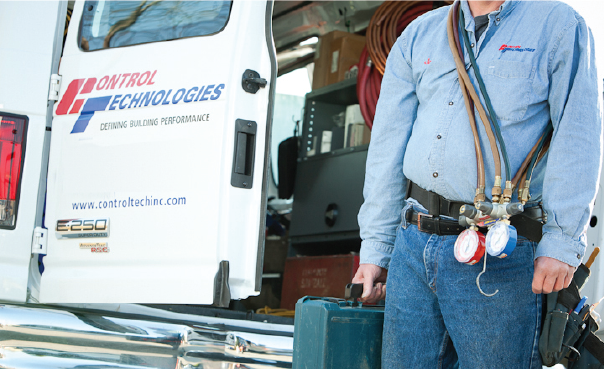 A Control Technologies service technician standing by a CTI van. Our service team is highly qualified and experienced.